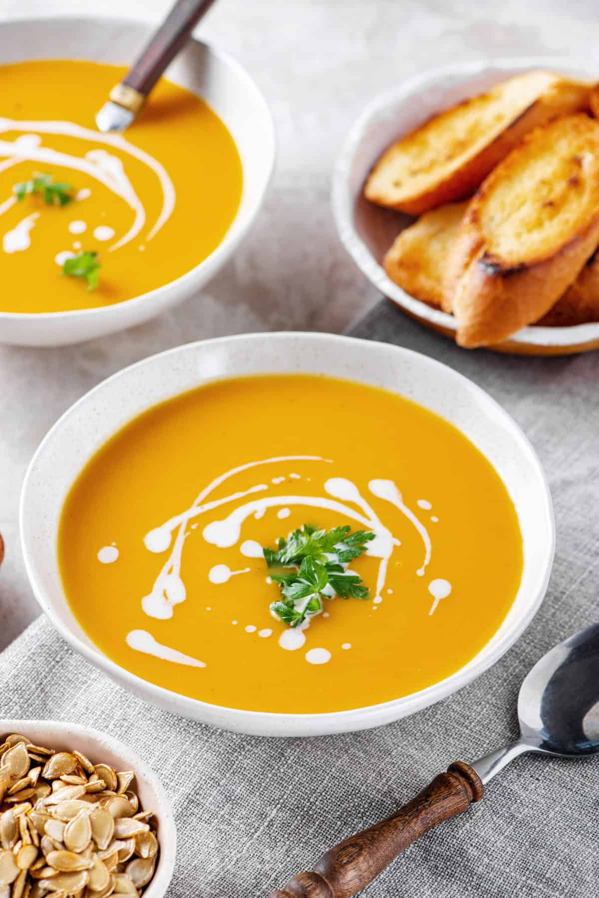 butternut squash soup with a sour cream swirl design and cilantro served in a white bowl