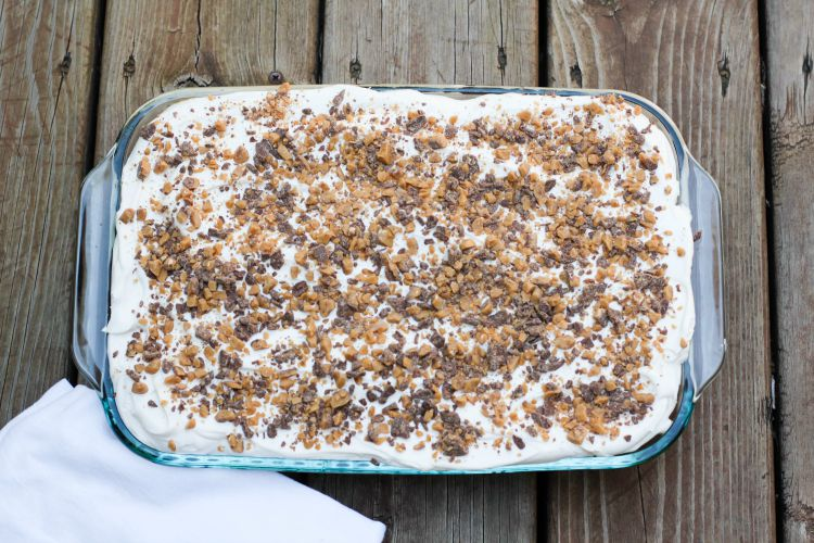 Cake in pan with whipped topping and crushed candy bar on top.