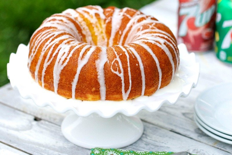 7UP Bundt Cake whole on a table with white plates and soda cans