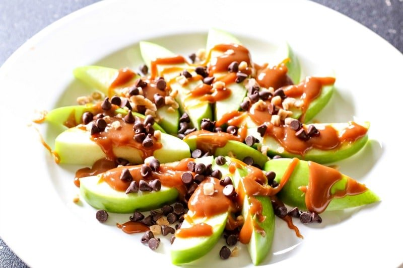 Round plate full of fall apple dessert known as loaded caramel apples