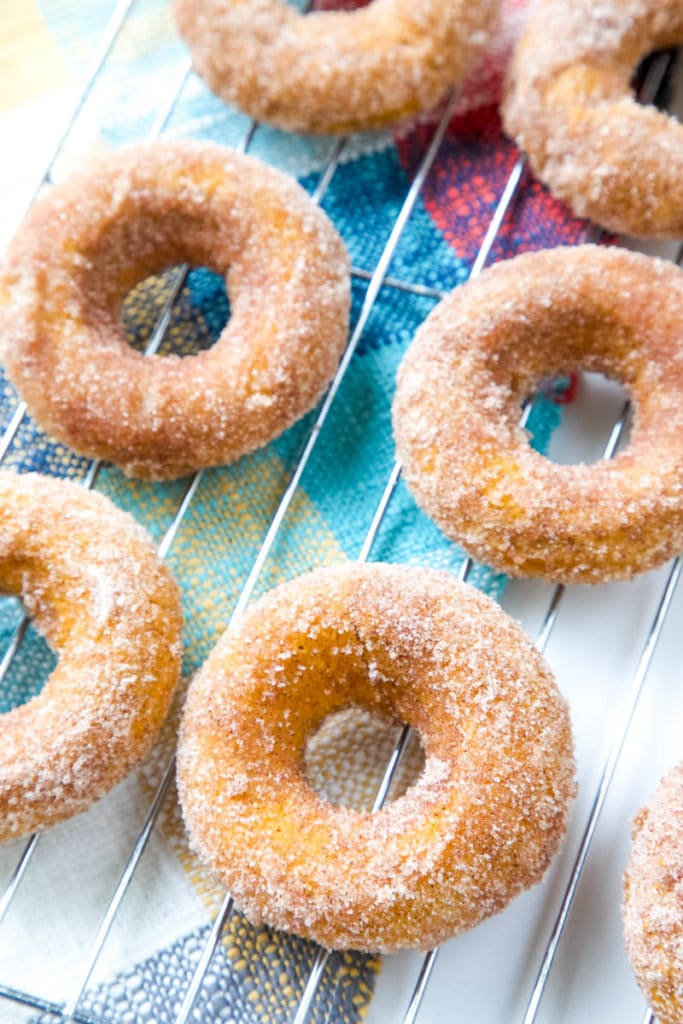 Pumpkin spice donuts on cooling rack.
