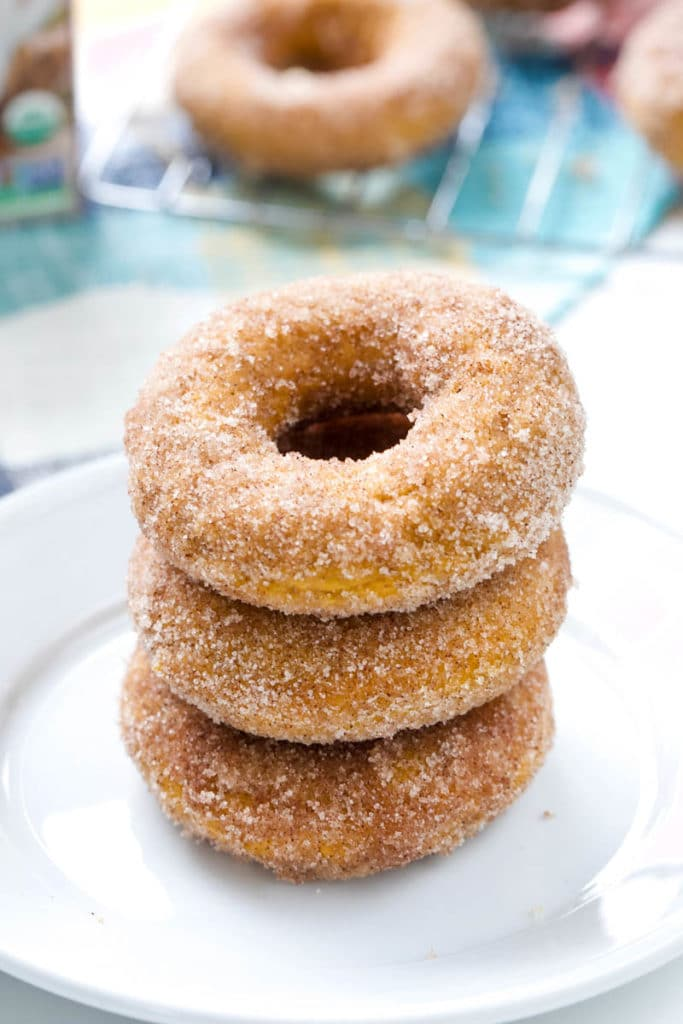 Stack of pumpkin doughnuts on a white plate