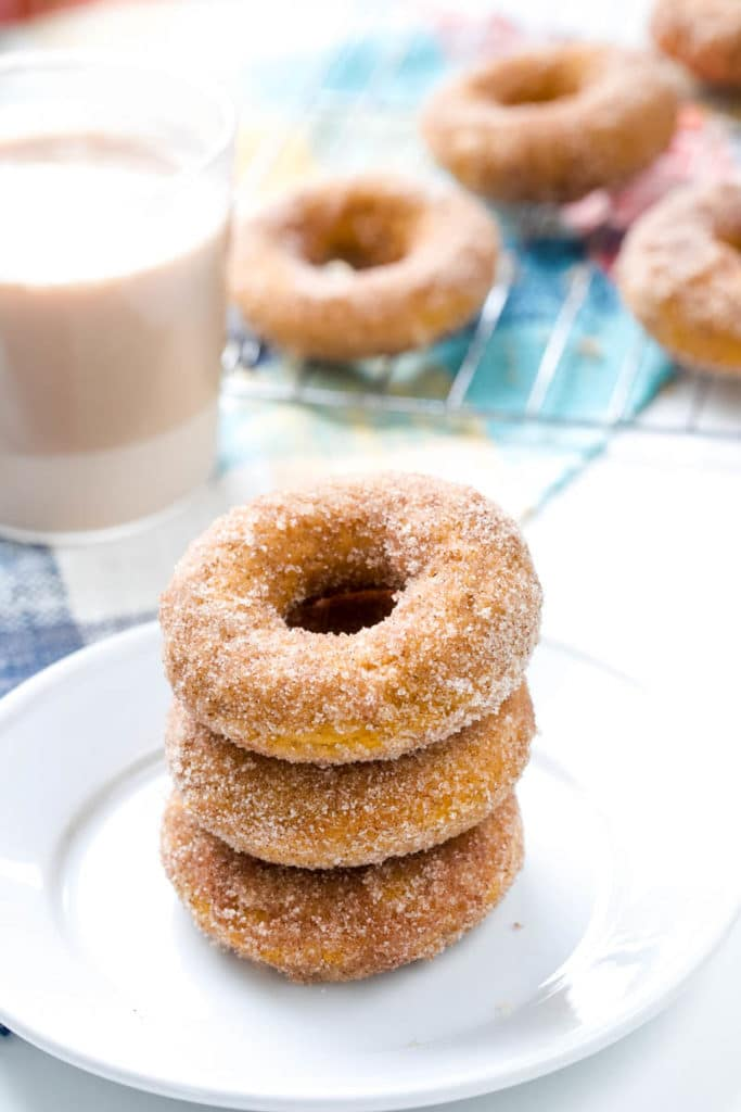 Three pumpkin donuts on a while plate.