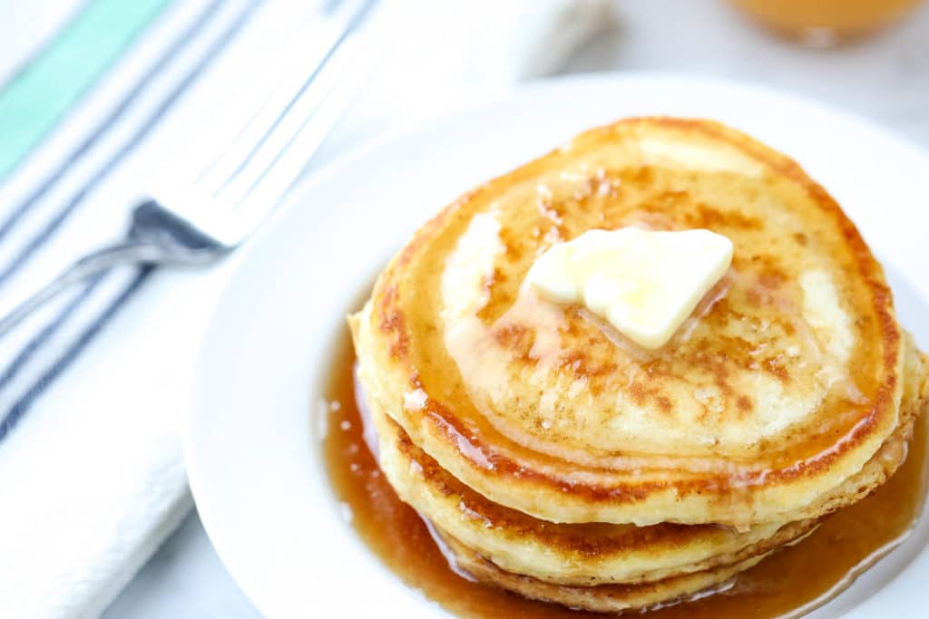 fluffy pancakes on a white plate