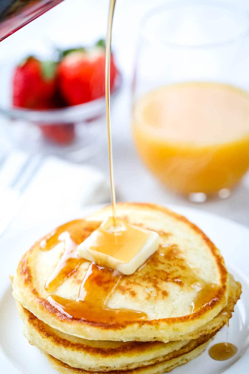 homemade pancakes on a white plate with orange juice and strawberries