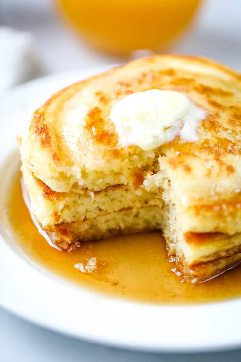 pancakes on a white plate cut into with butter and syrup