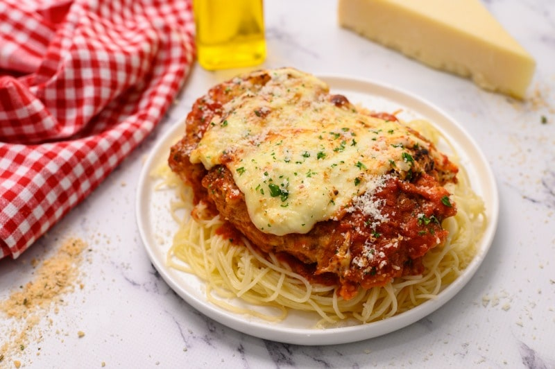 The Best Baked Chicken Parmesan recipe is made with breaded chicken cutlets that are browned on the stovetop and finished in the oven before being topped with marinara sauce and mozzarella cheese! The Best Baked Chicken Parmesan has a crispy coating made with Italian breadcrumbs and grated parmesan cheese, smothered in a store-bought marinara sauce and sliced mozzarella cheese for an easy dinner any night of the week!