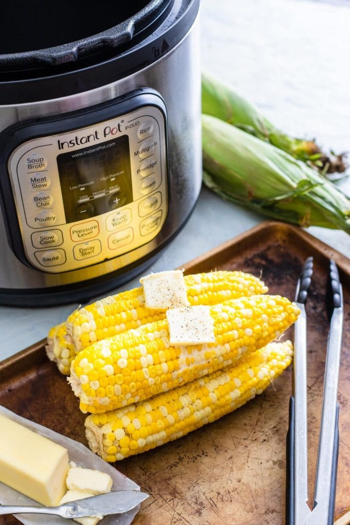 Fresh sweet corn on the cob in Instant Pot topped with butter.
