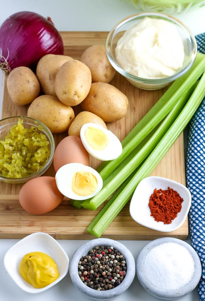 Potato salad ingredients on cutting board.