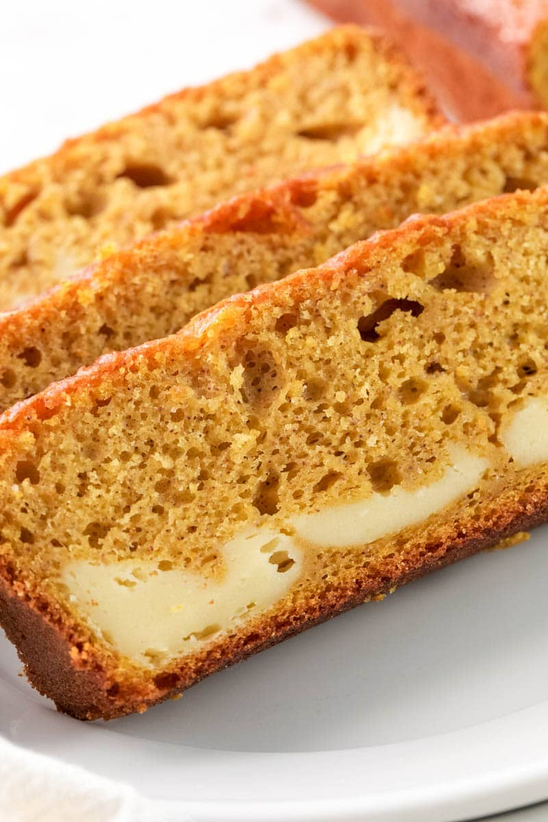 Three slices of pumpkin cream cheese bread on a white plate.