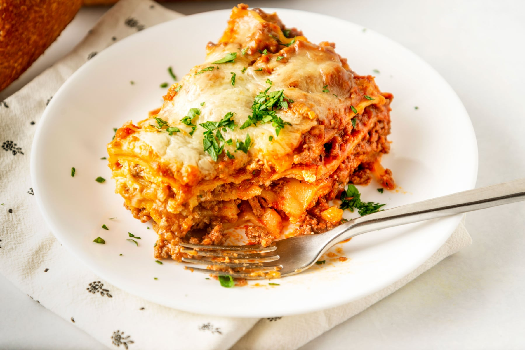 piece of slow cooker lasagna topped with cheese