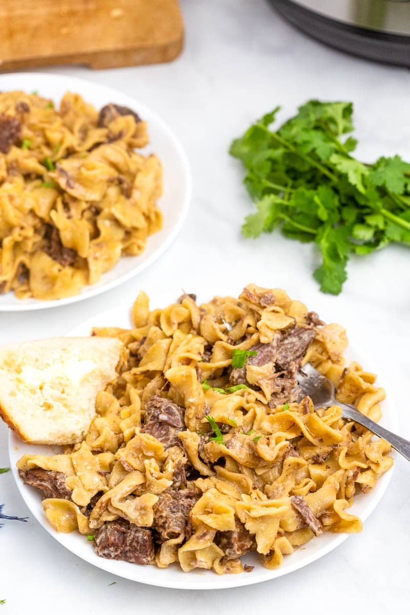 top shot of pasta and meat on white plate with buttered bread
