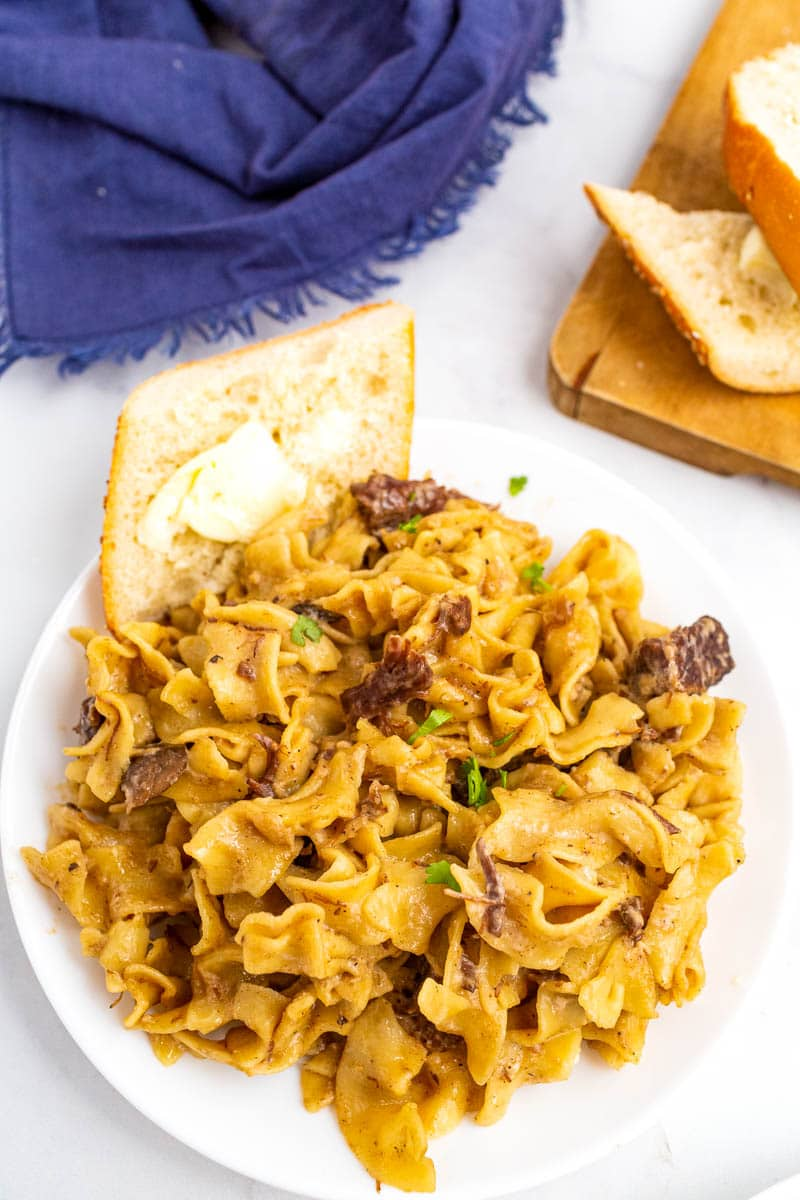 top shot of beef stroganoff on white plate with buttered bread