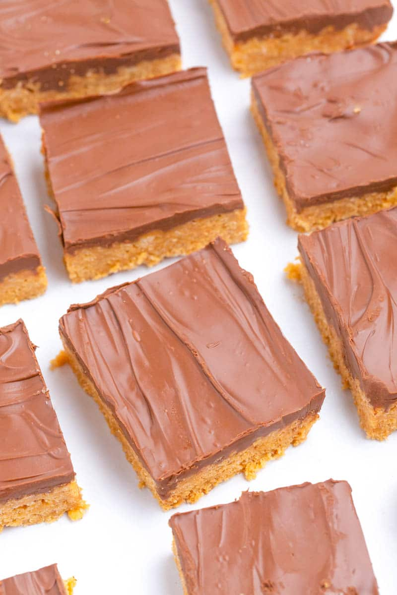 Chocolate covered peanut butter bars cut into squares on white table