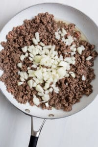 A top down view of a 12-inch skillet with browned beef and chopped yellow onion.