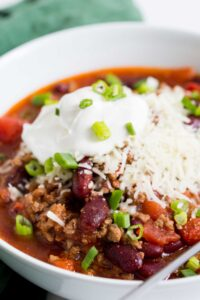 Close up image of crock pot chili in a white bowl with a silver spoon. This ground beef and bean chili is topped with shredded cheddar cheese, sour cream, and fresh scallions.