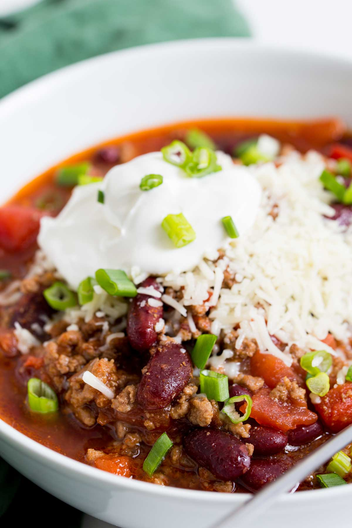 Close up image of crock pot chili in a white bowl with a silver spoon
