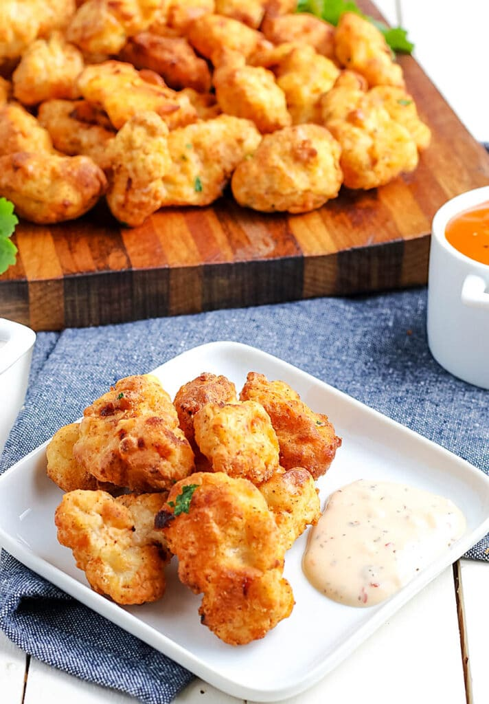 air fryer popcorn chicken bites on a white plate with dipping sauces