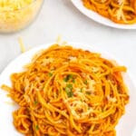 top shot of spaghetti in red meat sauce on white plate
