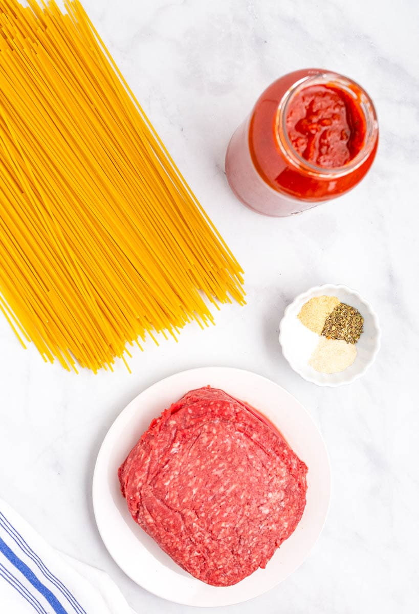 top shot of ingredients for spaghetti laid out on white countertop