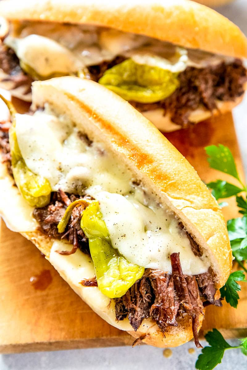 Closeup shot of beef sandwiches with peppers and cheese on wooden cutting block.