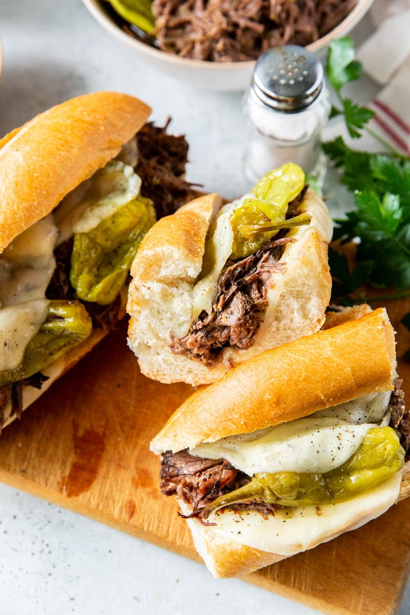 Two Mississippi roast sandwiches with peppers and cheese on wooden cutting block.