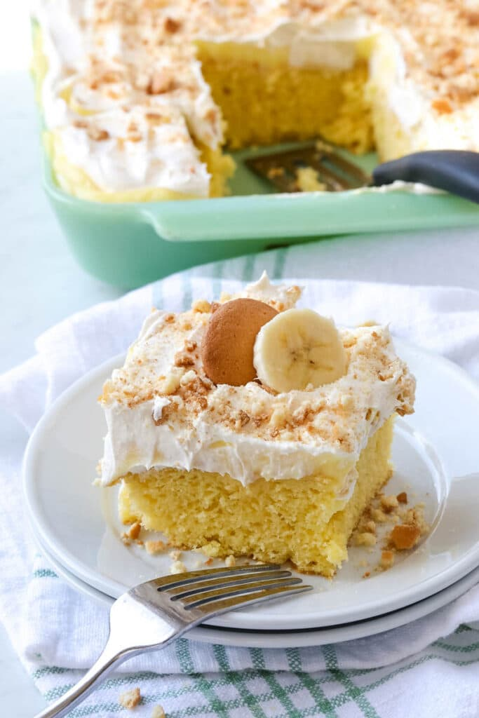 A square piece of banana pudding cake is placed on a white plate.