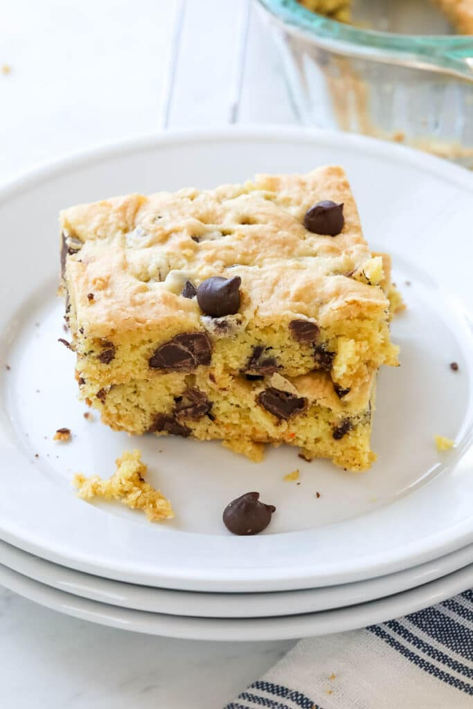 A chocolate chip cake mix cookie bar is on a white plate.