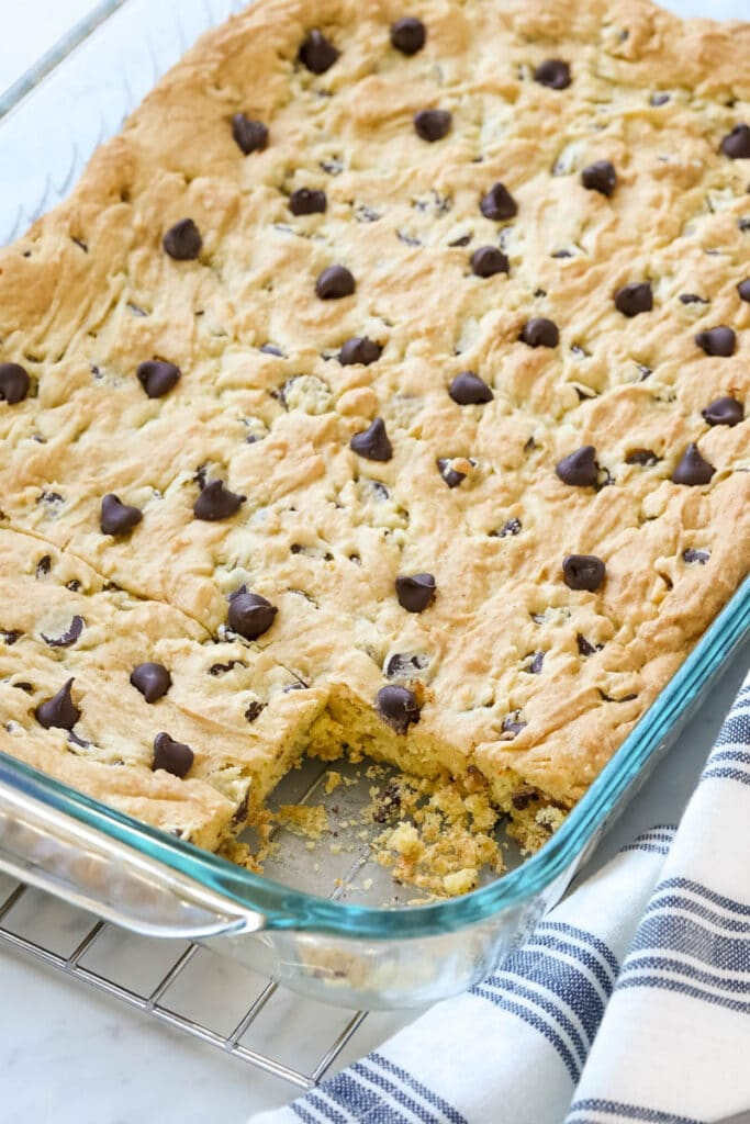 A glass baking dish is filled with baked cookie bars, and a single bar is missing from the pan.