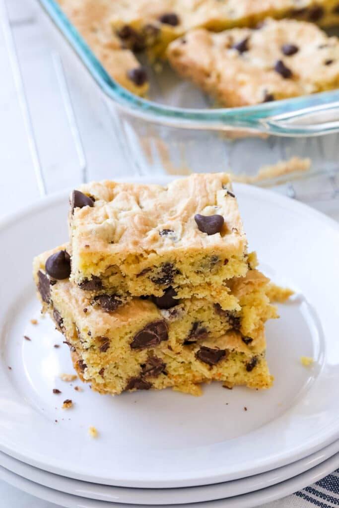 Cookie cake mix bars are stacked on a small white plate.