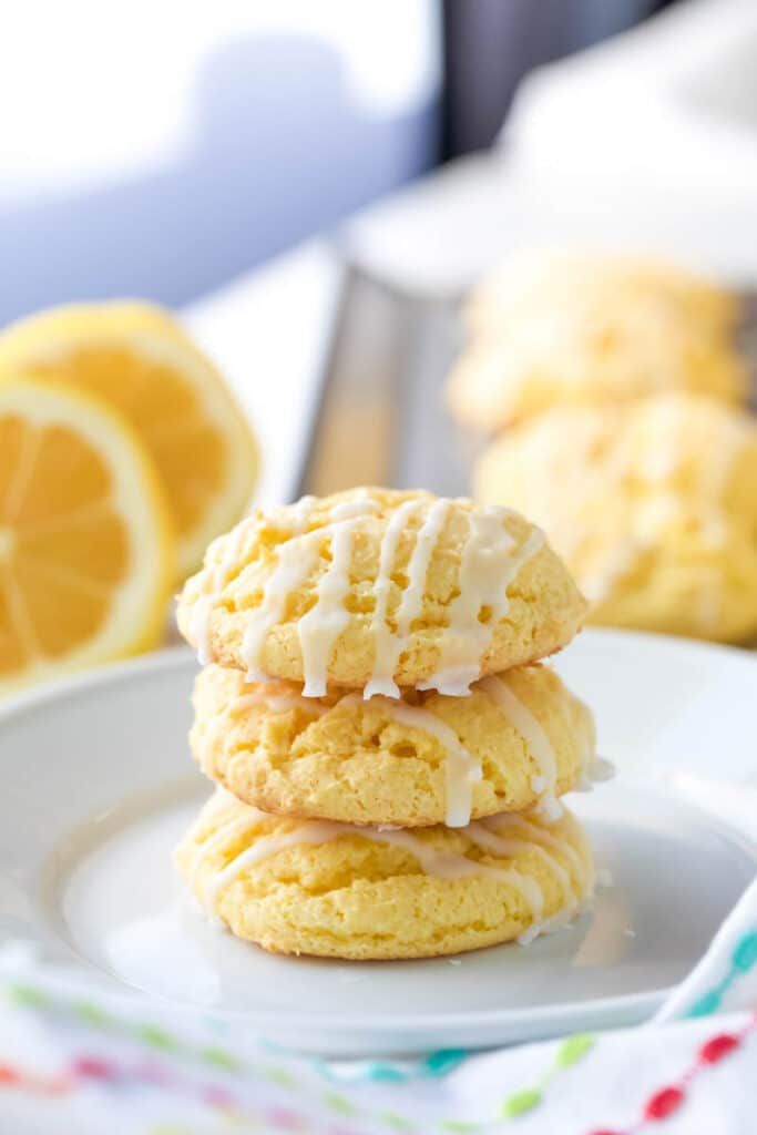 Three cake mix lemon cookies are stacked on top of each other on a white plate.