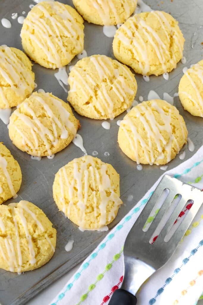Twelve lemon cookies are on a metal sheet pan, next to a spatula.
