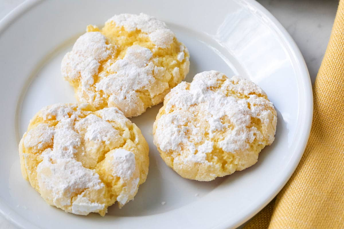 3 crinkle cookies laying on a white plate with a yellow napkin