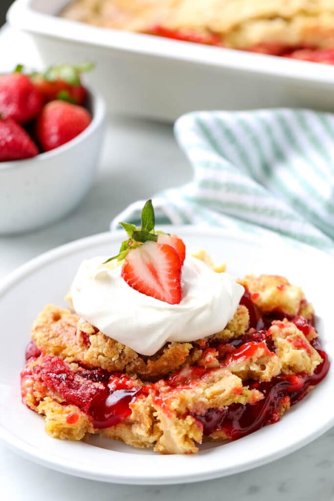 A serving of strawberry dump cake is presented on a white plate.