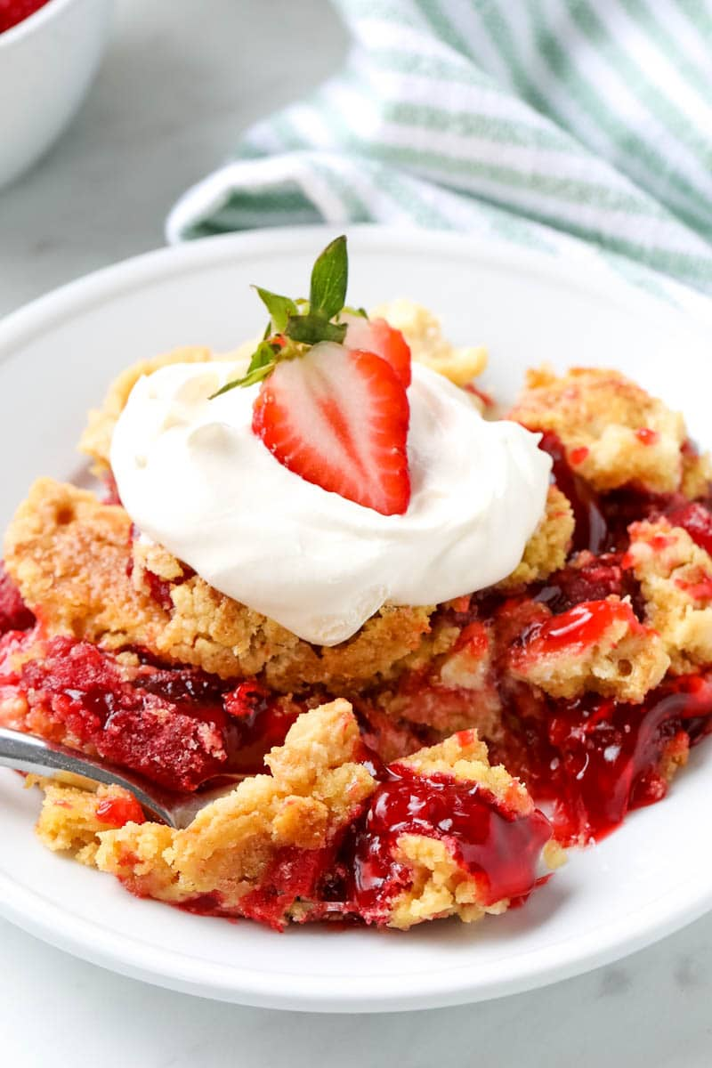 A serving of strawberry dump cake is garnished with whipped cream and a slice of strawberry.