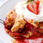 A spoon is placed into a serving of strawberry dump cake.