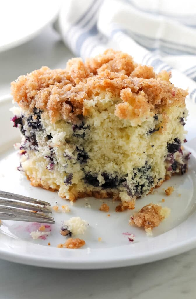 blueberry buckle on a white plate with a bite taken out