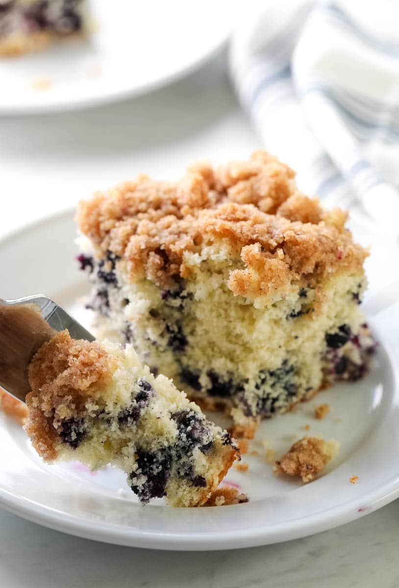 Blueberry buckle coffee cake slice closeup on a plate showing inside of cake with blueberries and struesel topping, with fork scooping a bite.