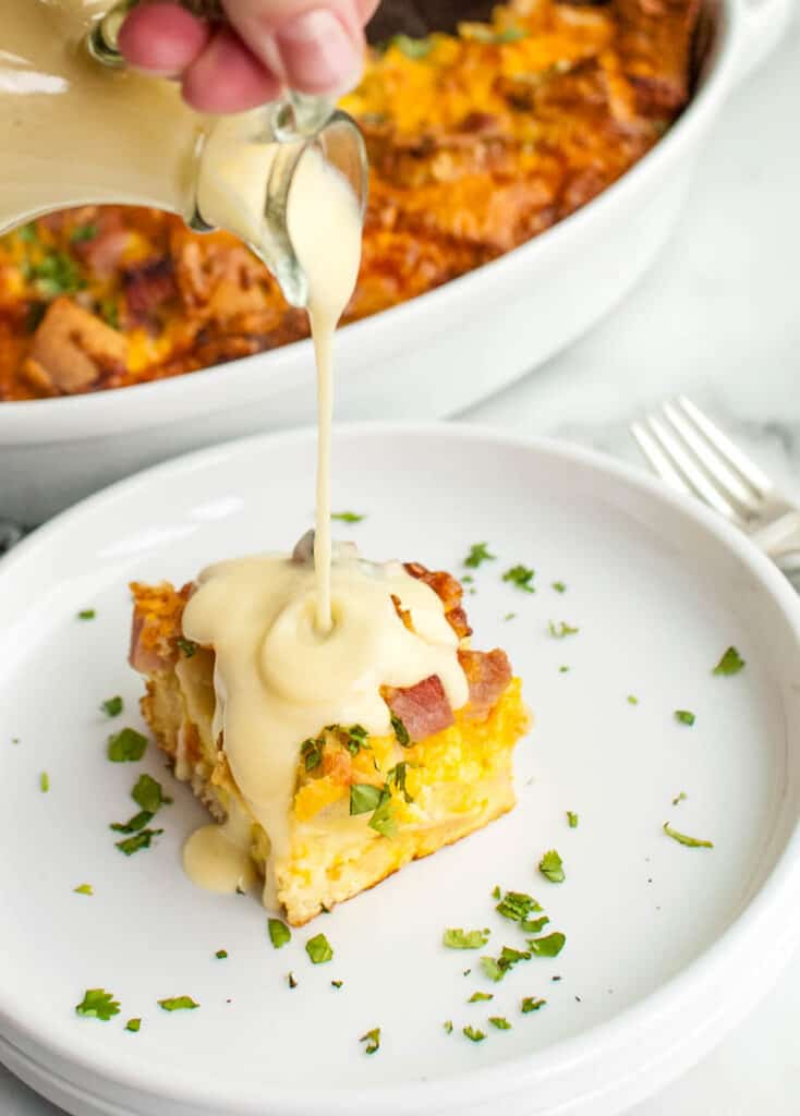 casserole with hollandaise sauce being poured over it