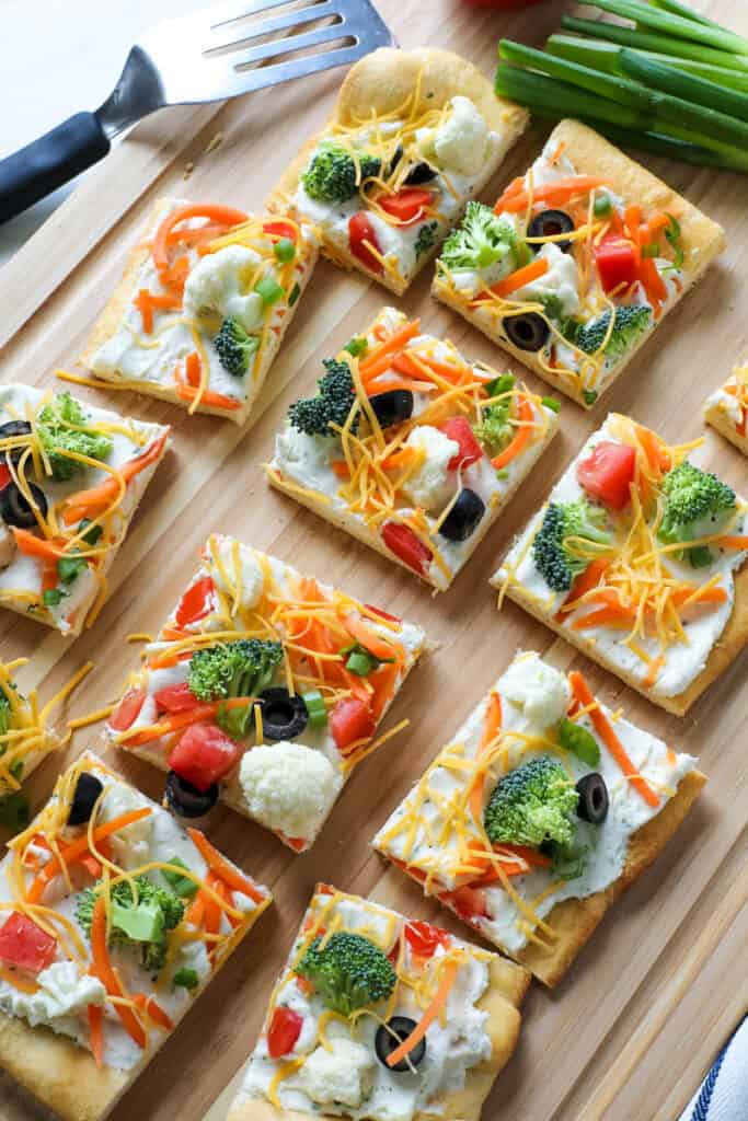 veggie pizza cut into pieces on a wooden cutting board