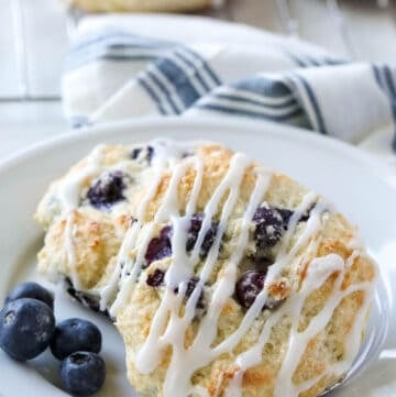 Bisquick Blueberry Biscuits on white plate with tea towel in background