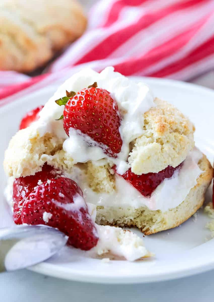 strawberry short cake with whipped cream on a white plate with a bite missing