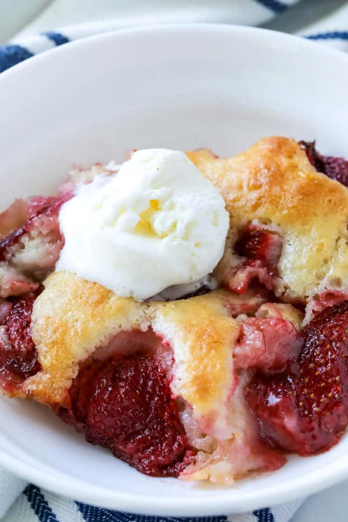 strawberry cobbler in a white bowl topped with vanilla ice cream