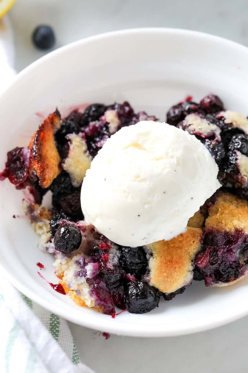 blueberry cobbler in a white bowl with a scoop of ice cream