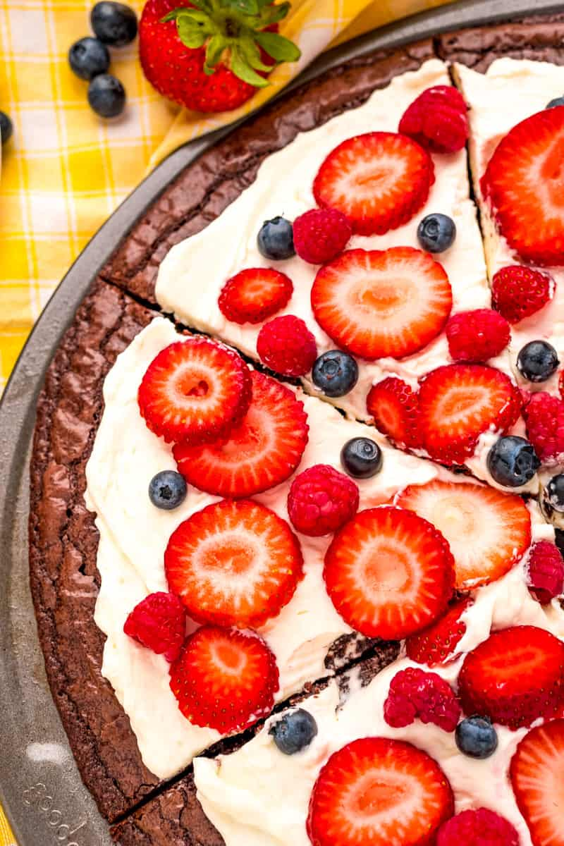 left side of a sliced brownie fruit pizza topped with raspberries, blueberries and sliced strawberries on the baking pan