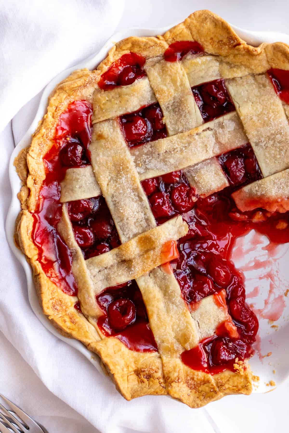 cherry pie with lattice design served in a white pie dish