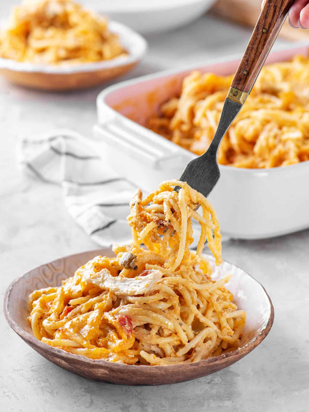 serving of chicken spaghetti served in a wood decorated bowl with a fork