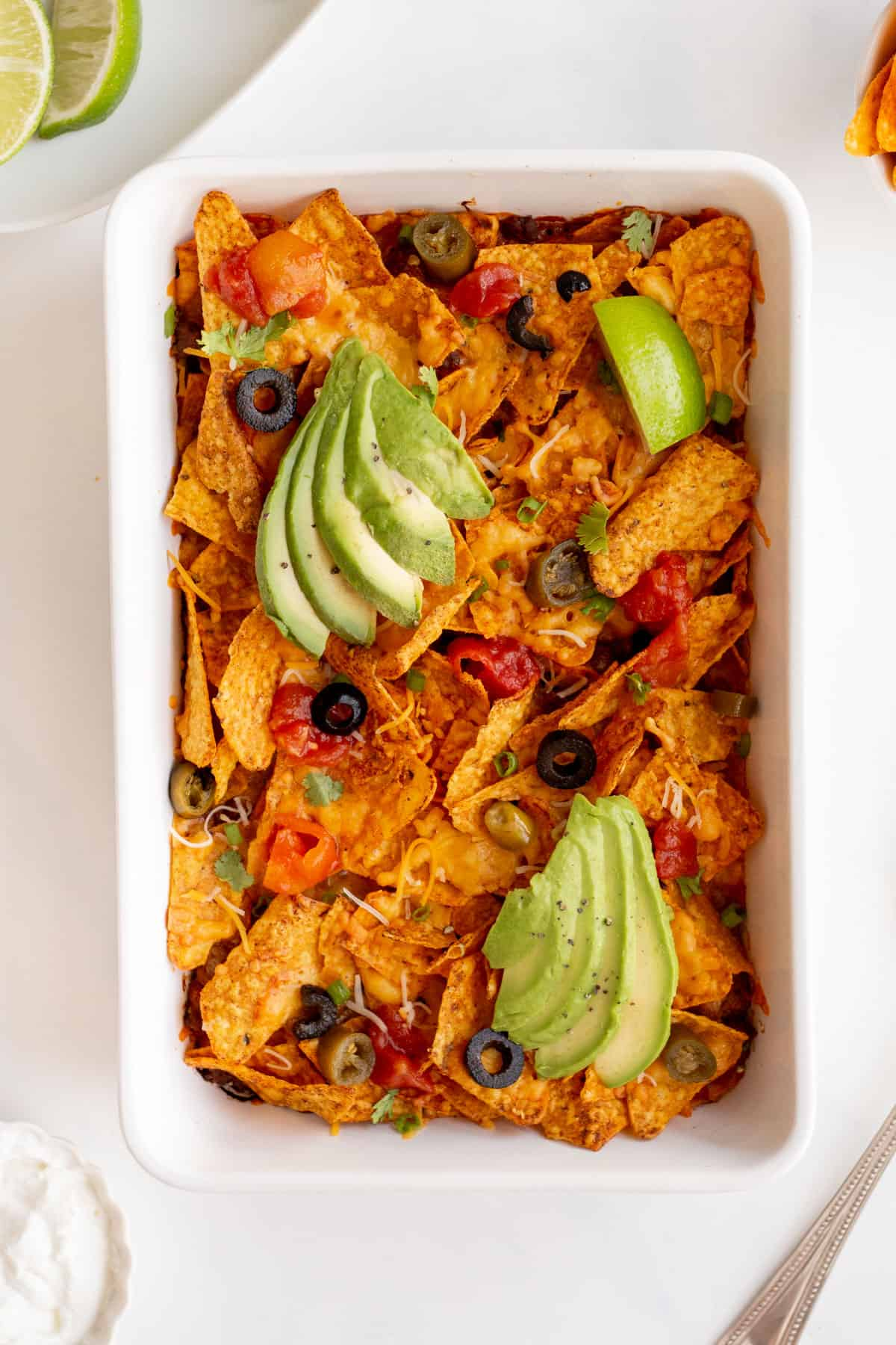 doritos casserole in a white rectangle dish, topped with sliced black olives, tomatoes, jalepenoes, avocados, cilantro, shredded cheese, and lime