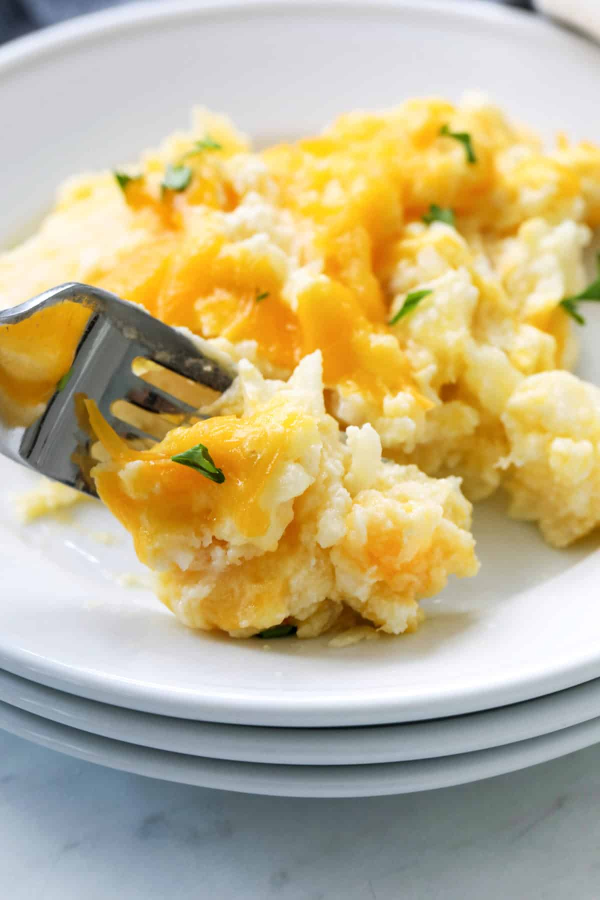 forkful of hashbrown casserole served on a white plate
