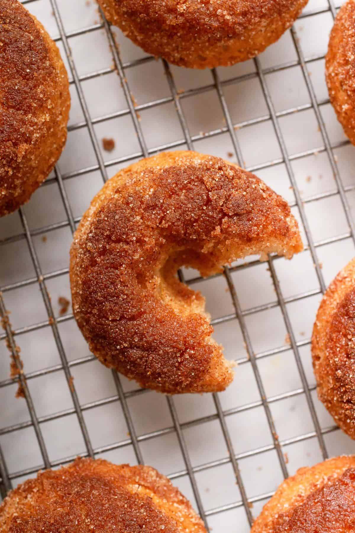 baked apple cider donuts sitting on a metal cooking rack. one donut has a bite taken out of it